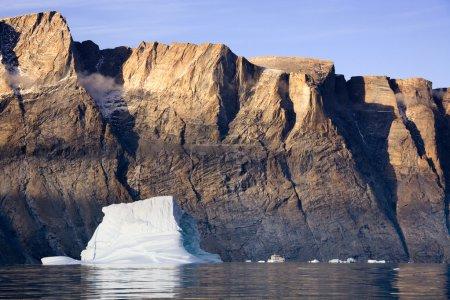 Photo pour Un brise-glace russe près d'un grand iceberg dans le fjord Franz Joseph dans l'est du Groenland. (Note taille du navire par rapport aux montagnes ) - image libre de droit