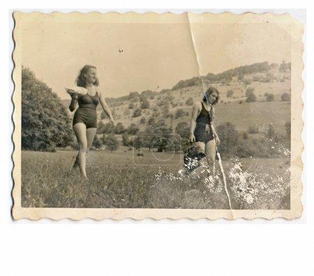 Friends - Two young women in bikini (walking through the meadow)