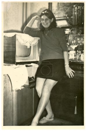 Partrait of an young woman - posing in front of the TV and turntable