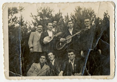 Photo for CENTRAL BULGARIA, BULGARIA - CIRCA 1950: Group of young men (one with a guitar, one with balalaika) posing in front of a pine forest - Note: slight blurriness, better at smaller sizes - circa 1950 - Royalty Free Image