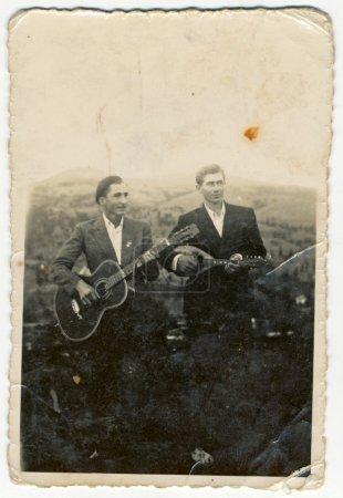 Friends play the guitar and balalaika