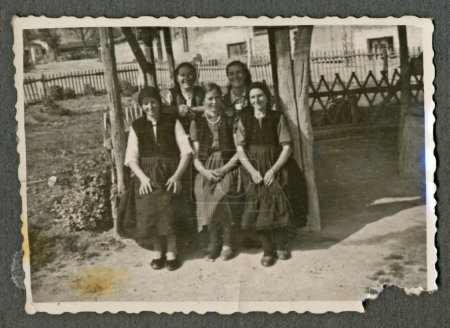 Young women sitting on an old wooden bench