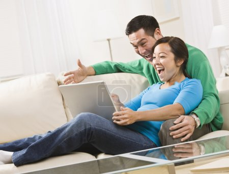 Photo pour Un séduisant jeune couple assis sur un canapé et Regarde un écran d'ordinateur portable. ils rient. tir encadrées horizontalement. - image libre de droit