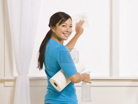 Photo pour Une séduisante asiatique jeune femelle lavage une fenêtre. elle tient un rouleau d'essuie-tout et a sa tête tournée à sourire vers la caméra. photo encadrée horizontalement. - image libre de droit