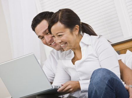 Happy Couple Sitting Together and Looking at a Laptop
