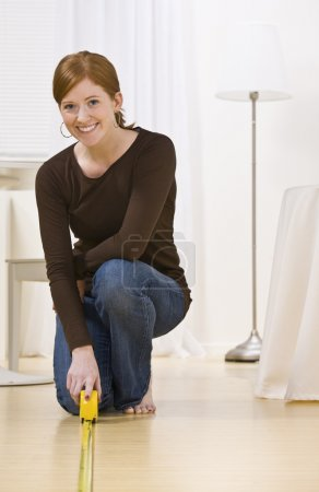 Attractive woman measuring floor