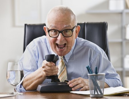 Foto de Un anciano empresario está sentado en un escritorio en su oficina y está bromeando. Él está mirando a una cámara. tiro horizontal enmarcado - Imagen libre de derechos