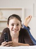 adolescent souriant tenant le téléphone portable