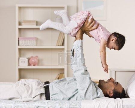 Photo pour Un père tient sa fille dans l'air au-dessus de lui. ils sourient à l'autre. photo encadrée carré. - image libre de droit