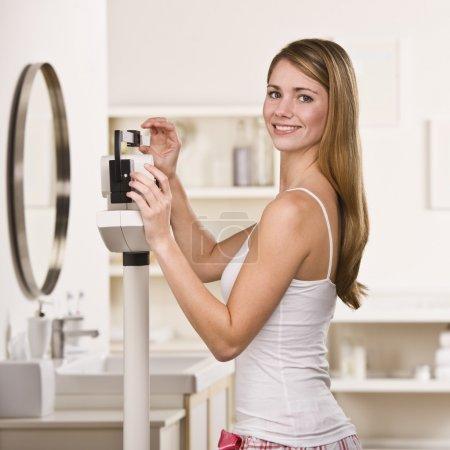 Photo pour Une jeune femme est debout sur un pèse-personne et contrôle son poids. Elle sourit à la caméra. photo encadrée carré - image libre de droit