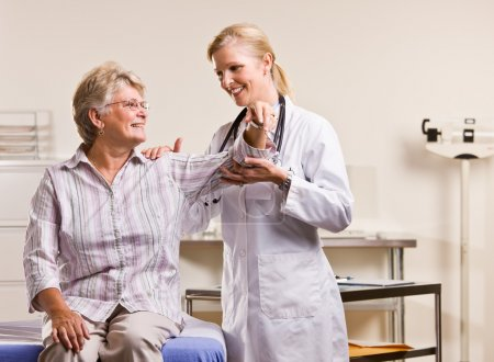 Doctor checking senior woman arm