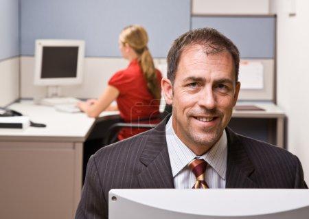 Businessman sitting at desk smiling