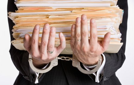 Businessman in handcuffs holding file folders