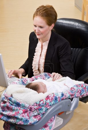 Businesswoman working with baby at desk