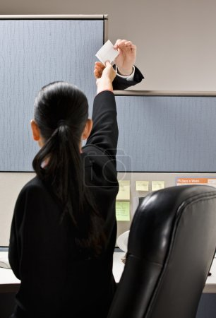 Businesswoman taking note from next cubicle