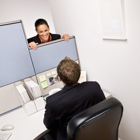 Businesswoman talking to co-worker in next cubicle