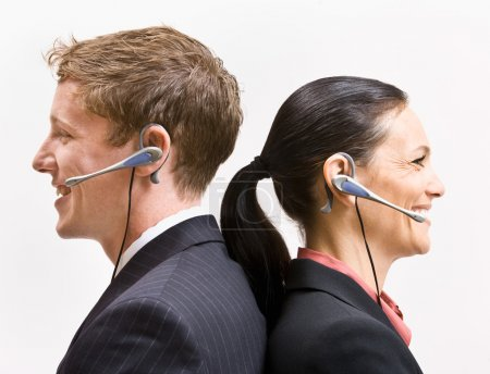 Business in headsets standing back to back