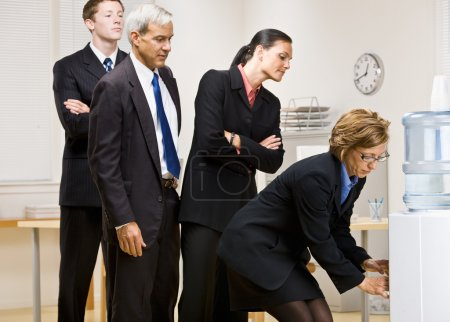 Business waiting turn at water cooler