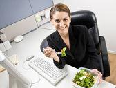femme d'affaires, manger salade au bureau