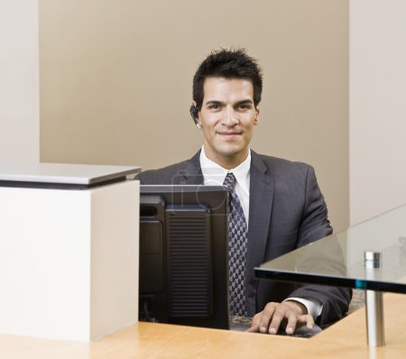 Photo pour Jeune homme en costume, assis au bureau. tir encadrées horizontalement. - image libre de droit