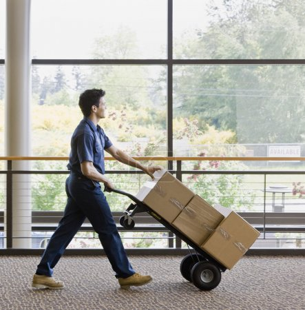 Photo for Young man using hand truck to move boxes. Vertically framed shot. - Royalty Free Image