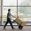 Young man using hand truck to move boxes. Vertically framed shot.
