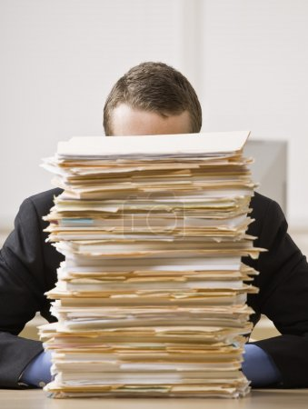 Businessman Behind Stack of File Folders