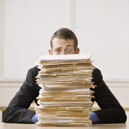 Photo pour Homme d'affaires derrière la grande cheminée de dossiers. format carré. - image libre de droit