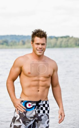 Photo pour Homme en maillot de bain pataugeant dans le lac - image libre de droit