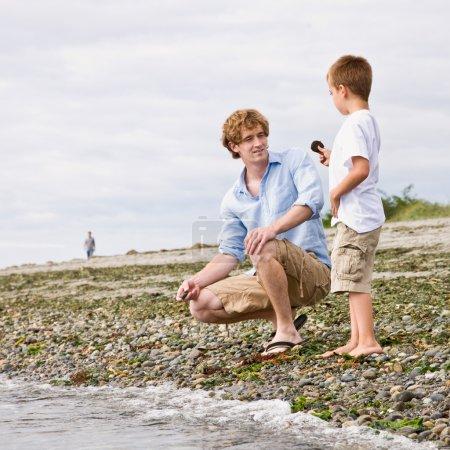 Photo pour Père et fils, collecte des rochers à la plage - image libre de droit