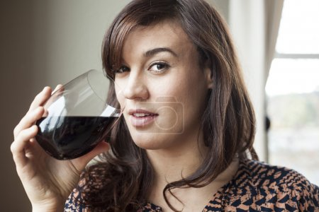Beautiful Young Woman in Drinking Red Wine