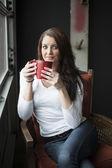 Mladá žena s krásné modré oči pití kávy