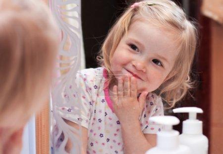 Photo pour Mignon bébé se lave le visage et se regarde dans le miroir - image libre de droit