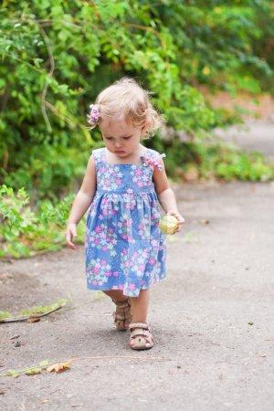 Photo pour Bébé mignon en mouvement avec une pomme dans la main - image libre de droit