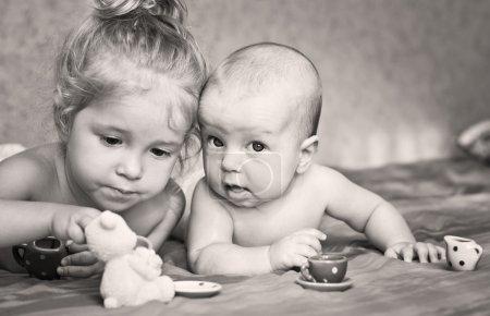 Photo pour Petite fille mignonne joue avec son jeune frère à la maison couché sur le lit avec des tasses - image libre de droit