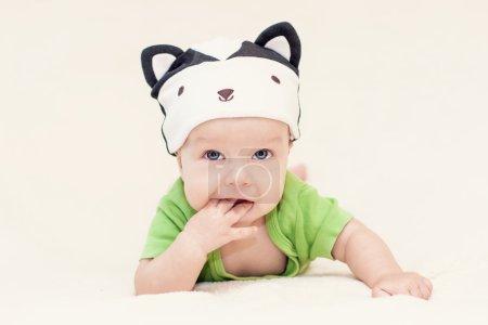 Foto de Bebé en la skunk sombrero acostada sobre su estómago - Imagen libre de derechos