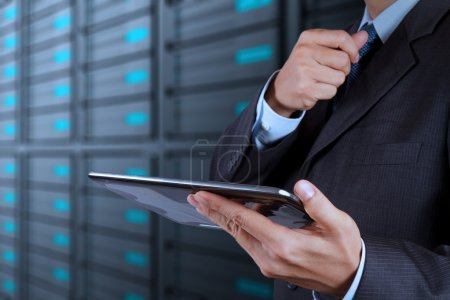 Photo for Businessman hand using tablet computer and server room background - Royalty Free Image