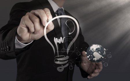 Photo pour Main d'homme d'affaires avec un stylo ampoule de dessin - image libre de droit