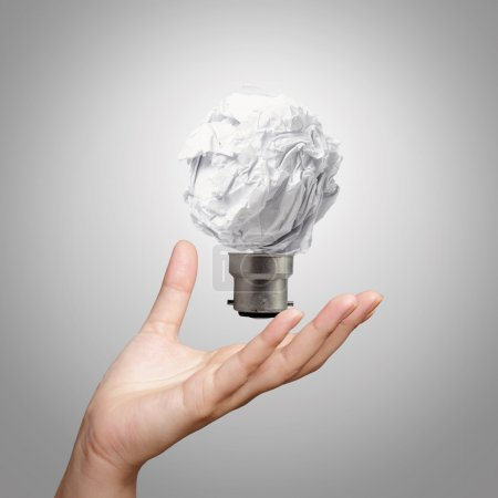 hand showing light bulb crumpled paper