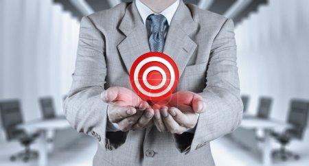 Businessman hand shows target symbol as business