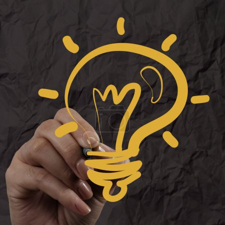 hand drawing light bulb with crumpled paper as creative concept