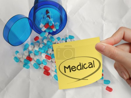 Photo for Hand holding medical sticky note on Pills spilling out of pill bottle crumpled paper background - Royalty Free Image