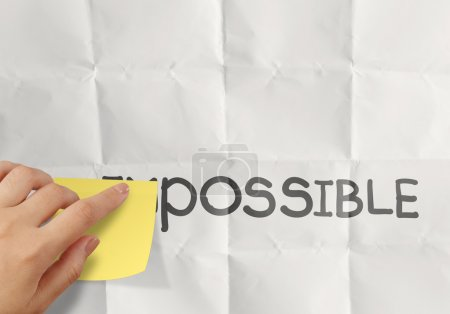 hand holding sticky note over word impossible transformed into p