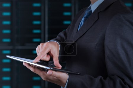 businessman hand using tablet computer and server room