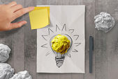 sticky note with another idea light bulb on crumpled paper as cr