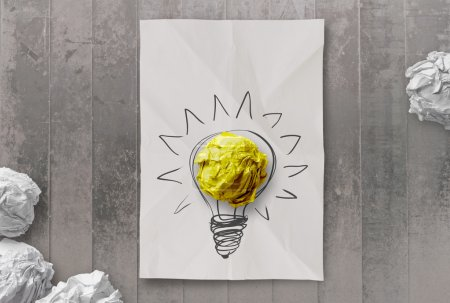Photo for Drawing light bulb on crumpled paper with workplace as creative concept - Royalty Free Image
