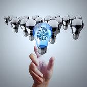 hand reach 3d metal brain inside  light bulb of leadership conce