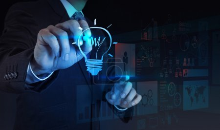 businessman hand draws lightbulb with new computer interface as