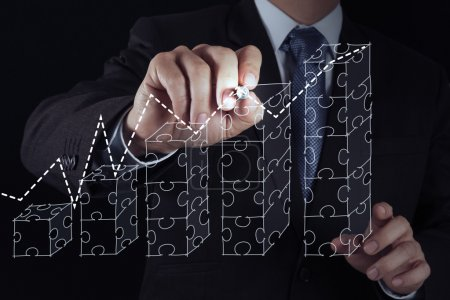 businessman hand puzzle charts with new modern computer and busi