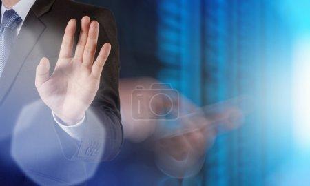businessman hand pressing a touchscreen button on server backgr